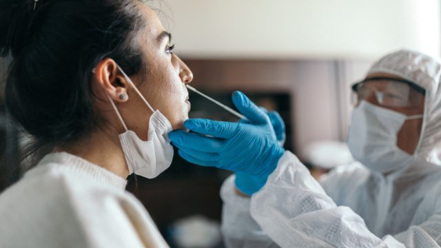 Doctor in protective workwear taking nose swab test from young woman