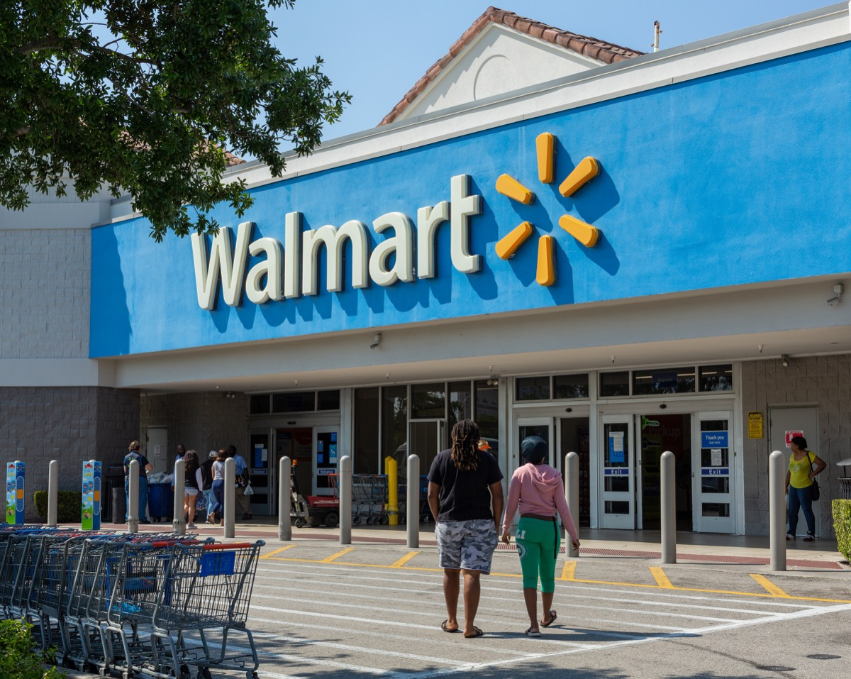 Miami, FL, USA - March 26, 2020: People going in a Walmart store on sunny day. Walmart is the world's third largest public corporation that runs chains of department stores. Quarantine due Coronavirus