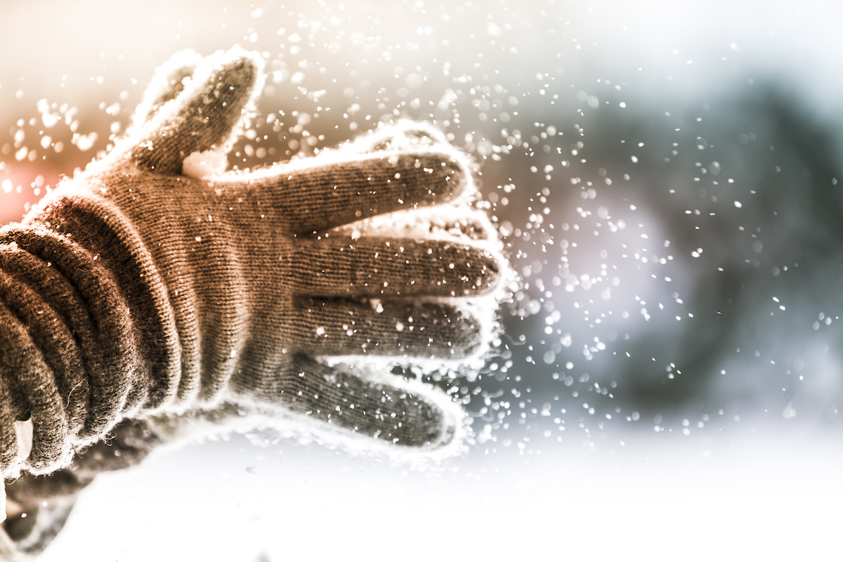 Closeup of person clapping winter gloves together as snow falls from them
