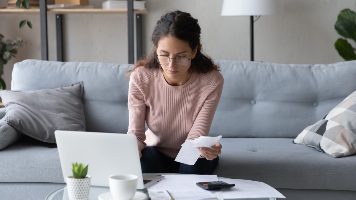 Serious young woman in glasses sit in living room pay bills taxes on laptop online, focused millennial female manage family expenditures expenses, plan budget on computer, make payment on web