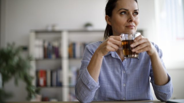 a woman sitting and drinking, glass filled with beverage