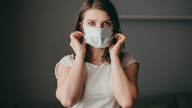 A young woman wearing a face mask while indoors.