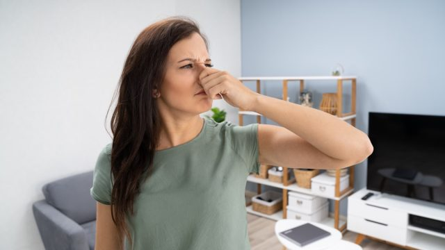 young woman in living room holding nose due to a bad smell