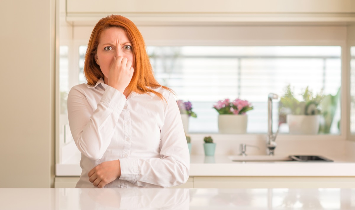 redheaded woman holding nose