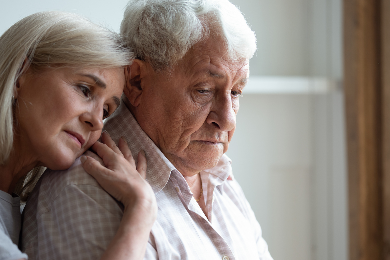 A middle-aged woman hugging an older man suffering from dementia