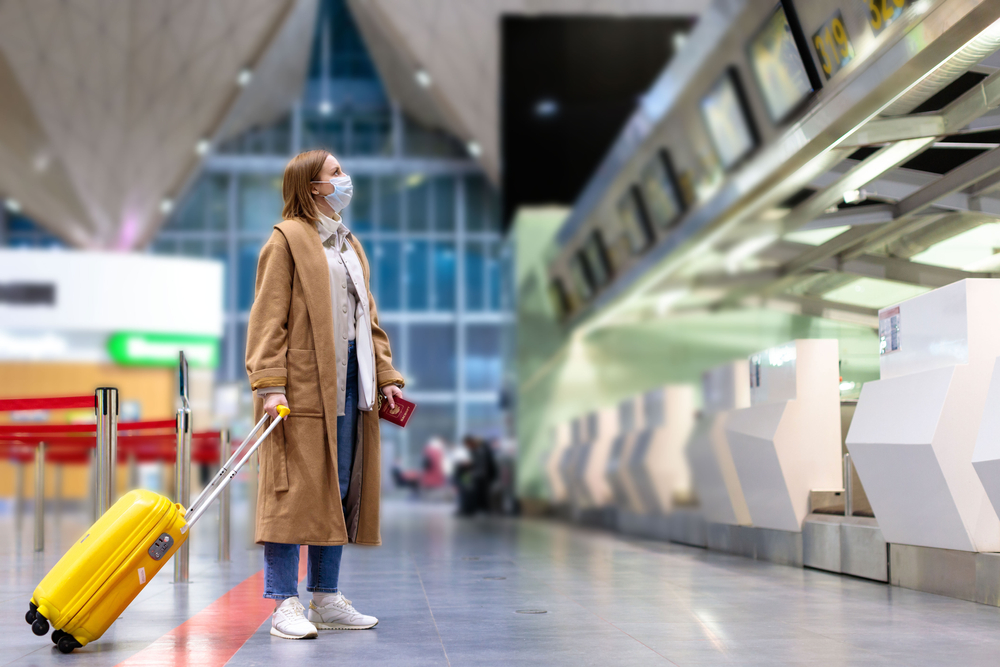 A woman wearing a face mask standing in an empty airport with her suitcase