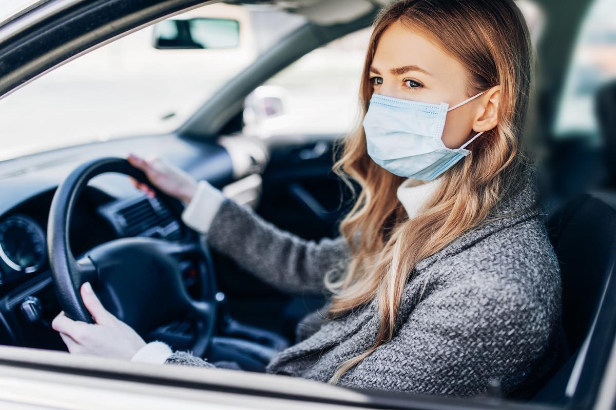 woman sitting inside a car, wearing a light blue mask