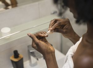 Unrecognizable woman looking at her nails, while removing her nail polish.