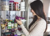 woman looking in cabinet and holding bottle with purple top