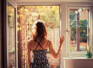 woman looking out door into garden