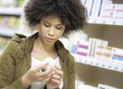 woman looking at supplement bottle