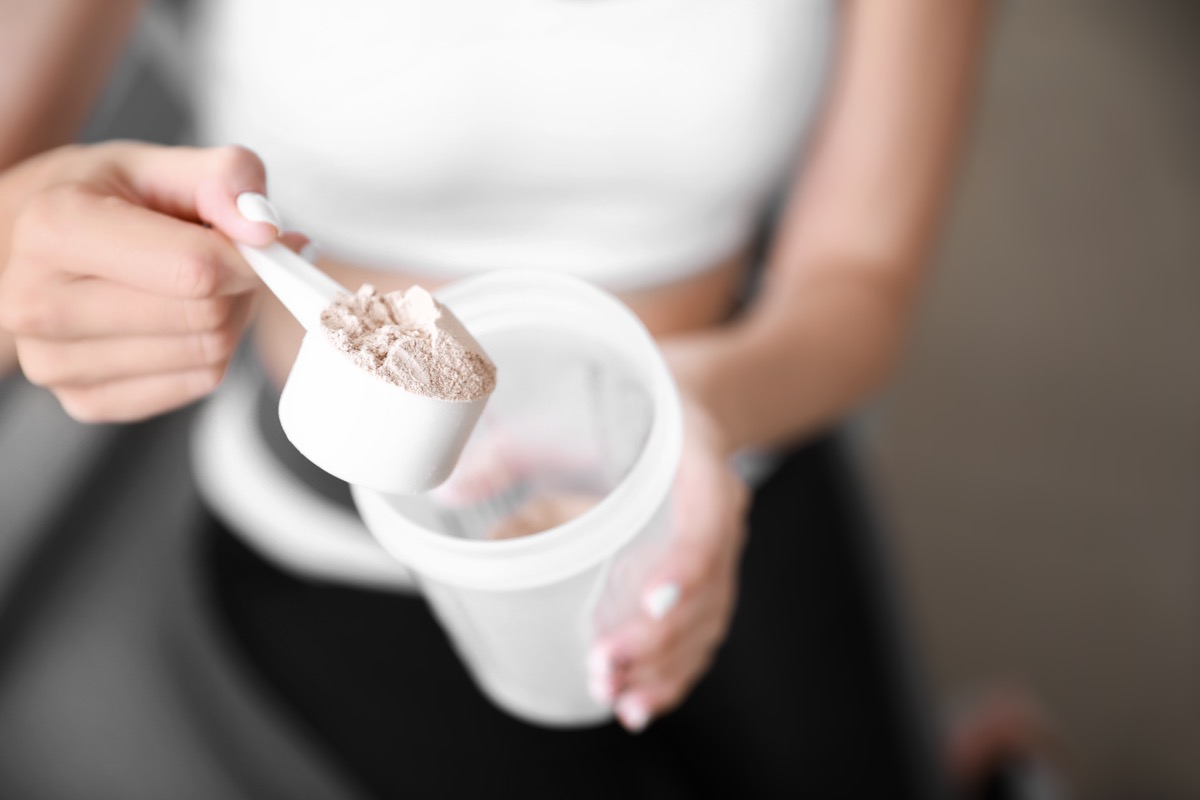 young woman preparing protein shake