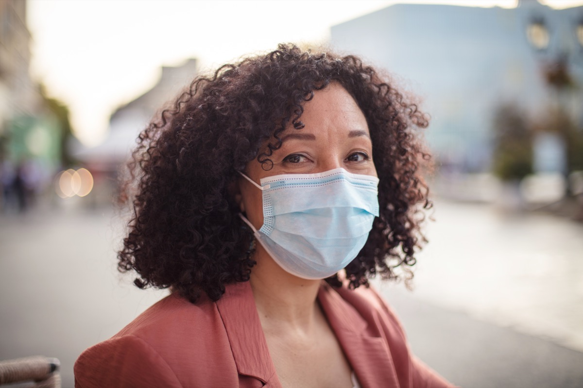 Woman with protective face mask sitting in café.