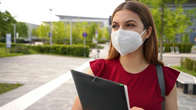 A woman wearing a face mask and holding a clip board about enter a school where mandates aren't allowed