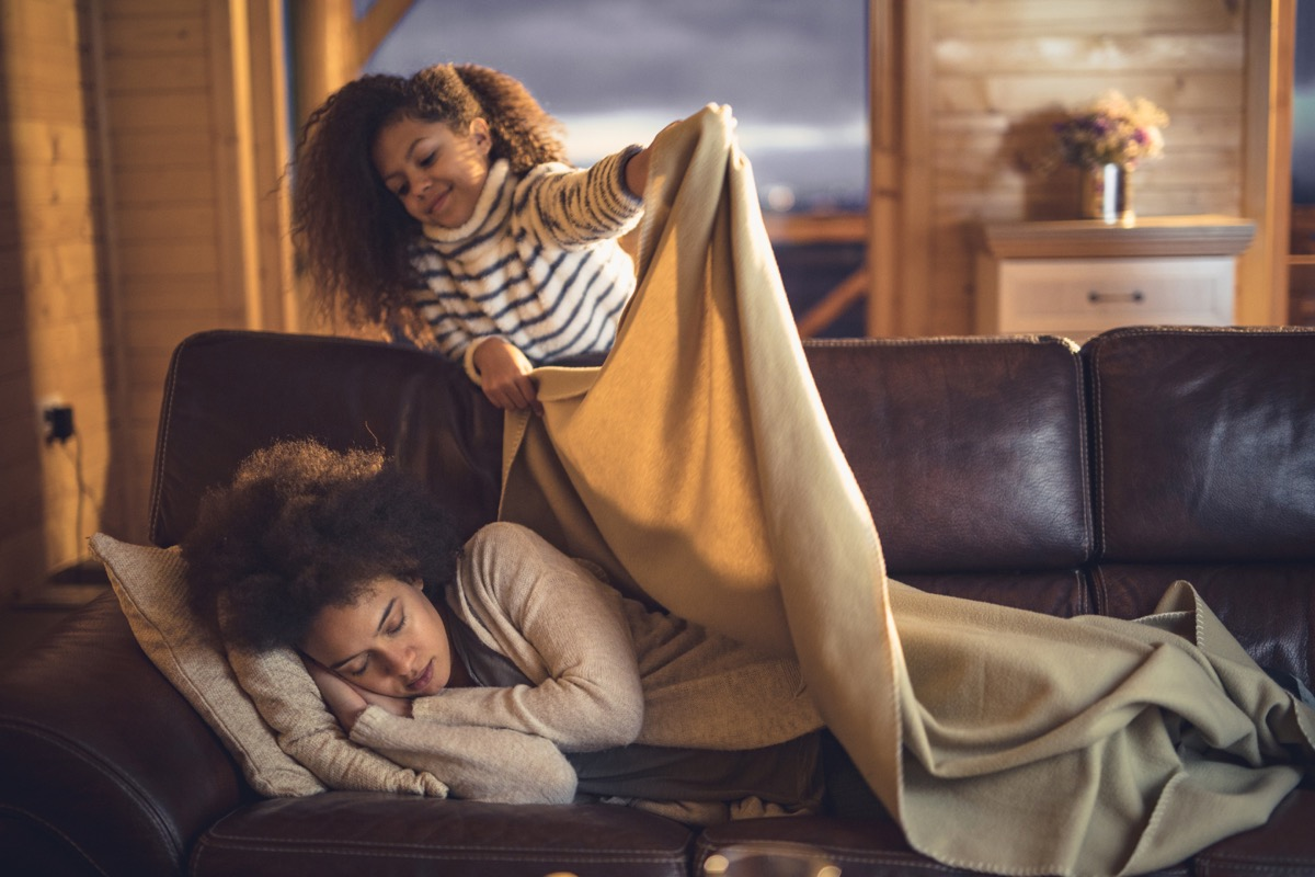 girl covering mother with blanket while she is sleeping on sofa at home. Focus is on woman.