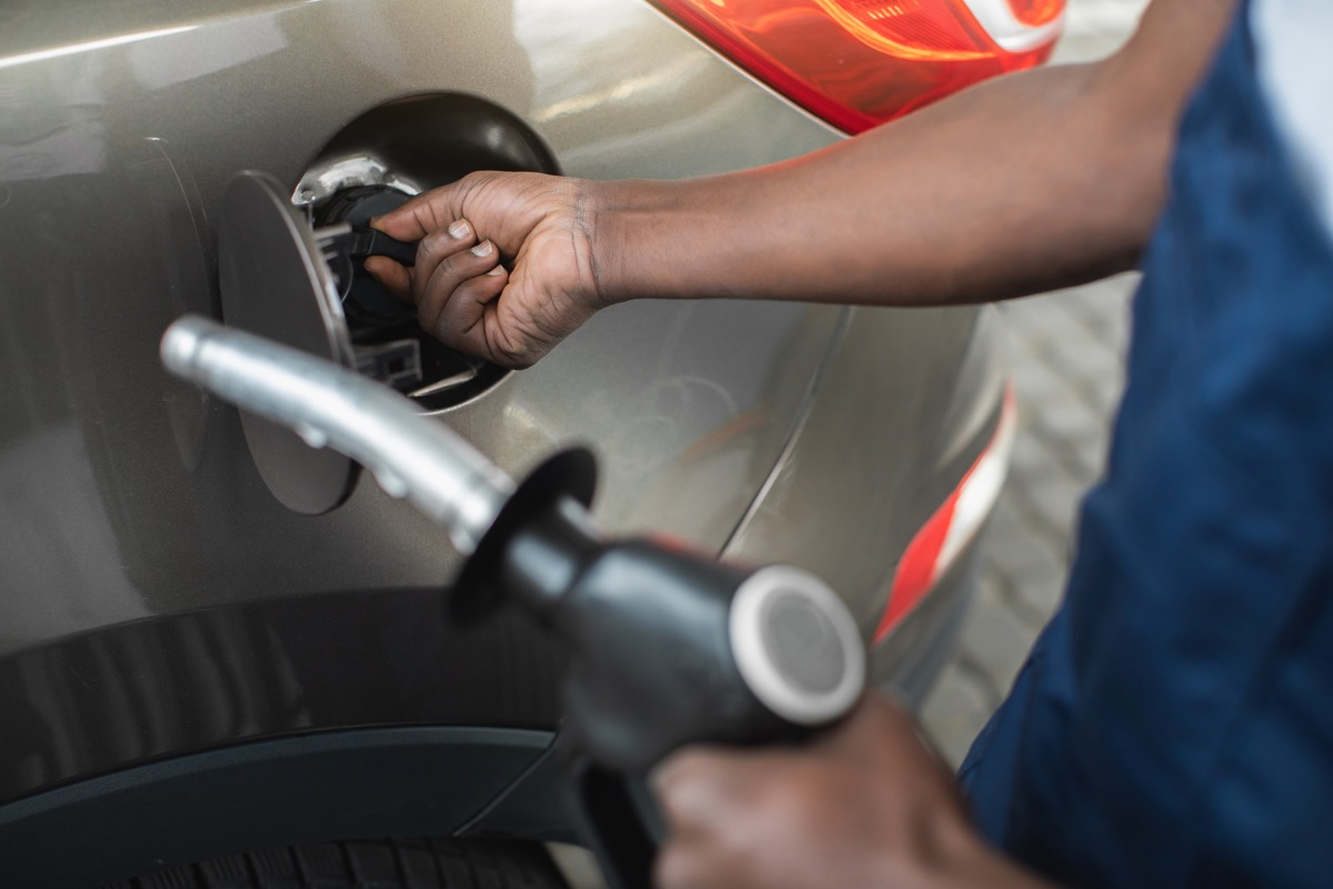 Close up cropped shot of a gas station worker's hands with filling gun, ready to refueling the car with gas or petrol at a gas station