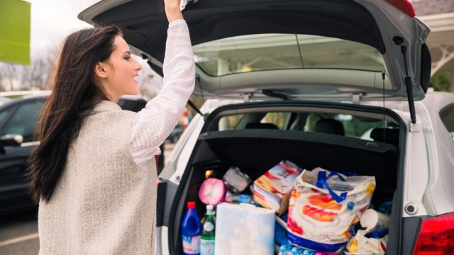 woman packing groceries into the trunk of her car