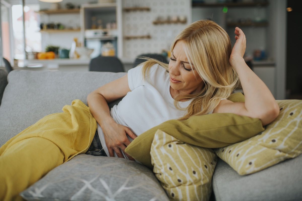 woman on couch with stomach pain