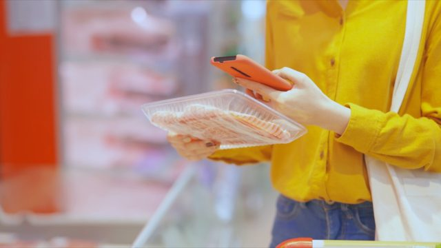 woman in yellow blouse shopping for meat in supermarket holding cell phone