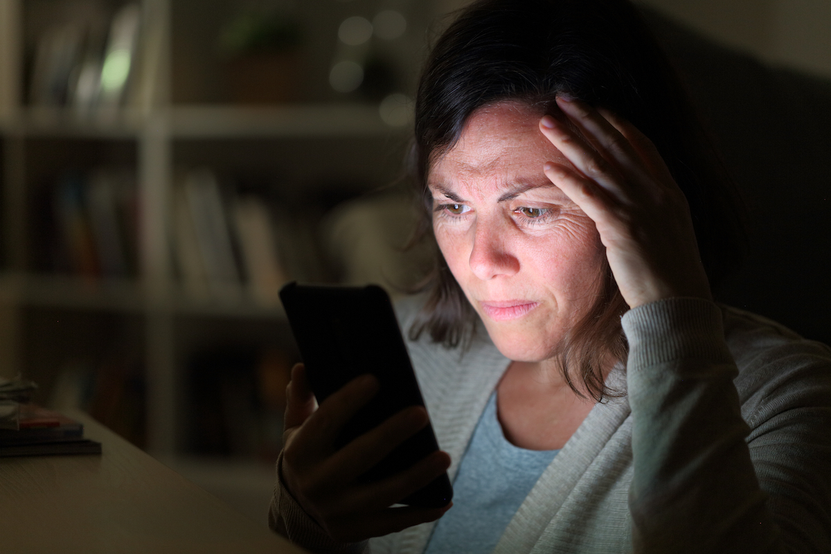 Woman reading on smart phone lighted screen sitting at night at home