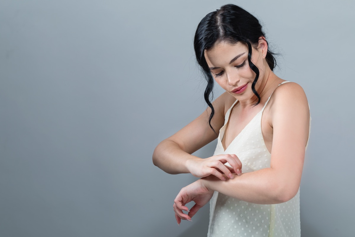 Young woman scratching her itchy arm. Skin problem. on a gray background