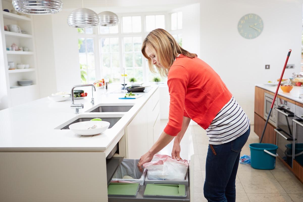 woman in kitchen, throwing away trash