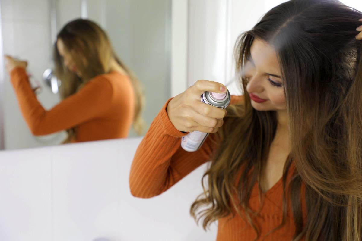 woman using hairspray on her hair