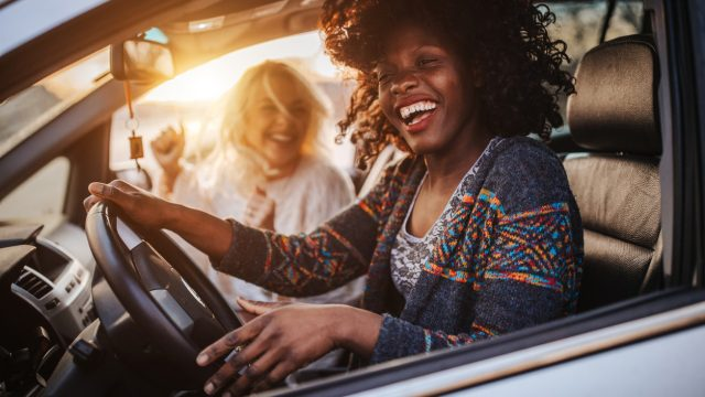 Two cheerful young women driving in a car
