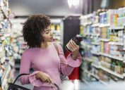 woman in her 20s shopping in a grocery store, carrying a shopping basket. She is reading the ingredient label on a bottle.