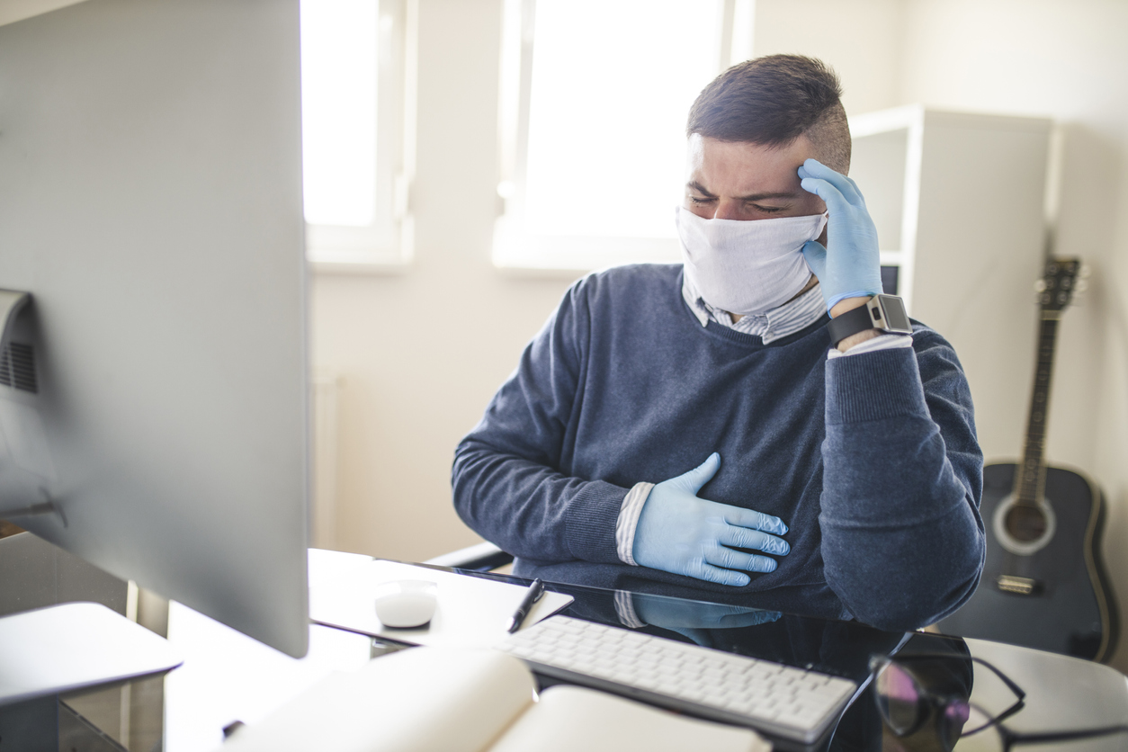 A young man sitting at a desk wearing a face mask and gloves grabbing his chest due