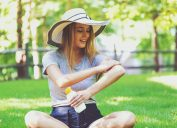 A young woman applying sunscreen to her arm while sitting outside in a field.