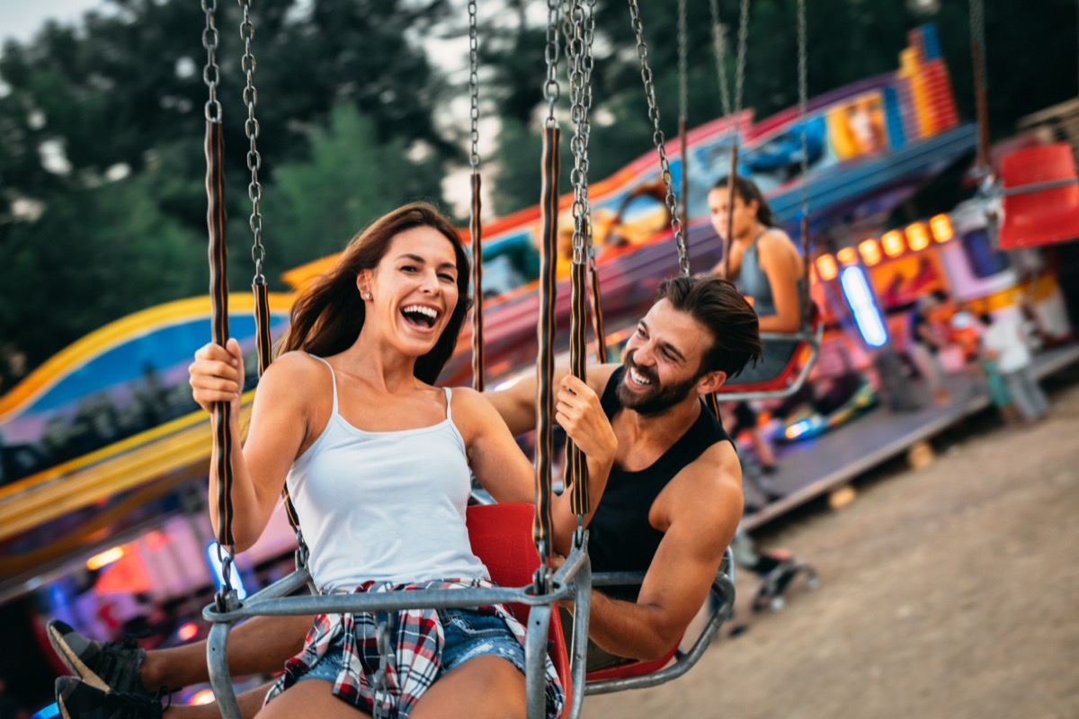 Man and woman riding swings at amusement park