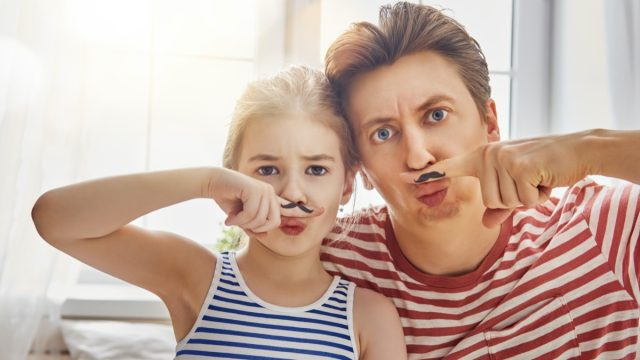 Father and young daughter with fake mustaches painted to their fingers