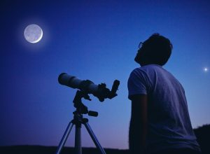 Man looking at moon with telescope