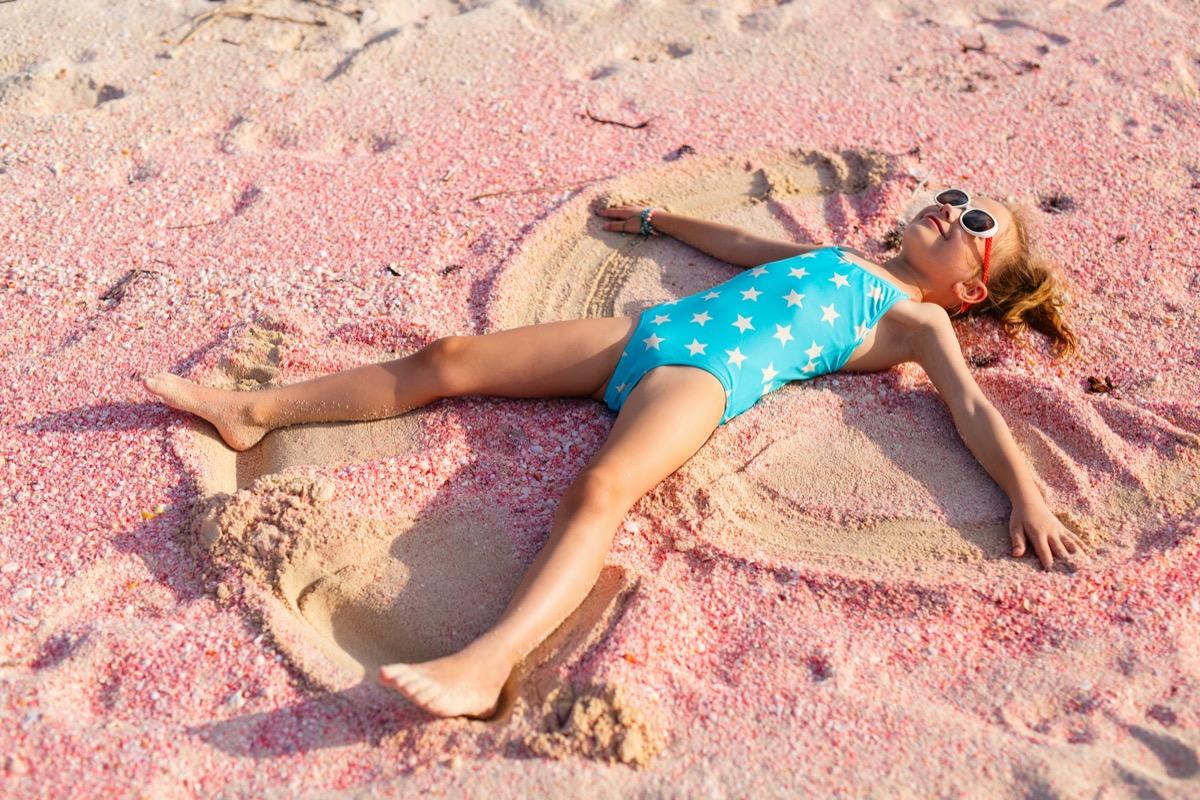 Little girl making sand angel on the beach