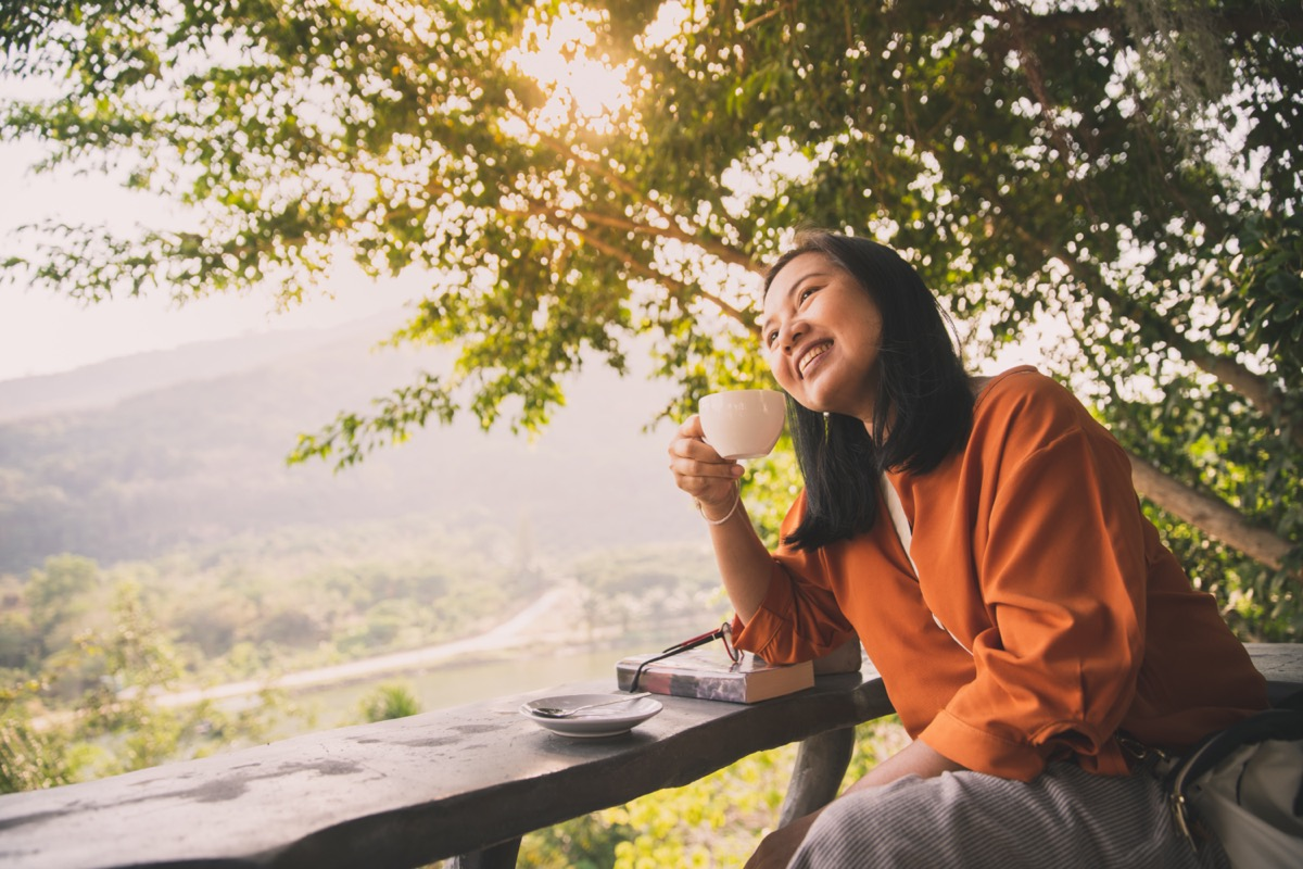 Woman drinking coffee in sunshine
