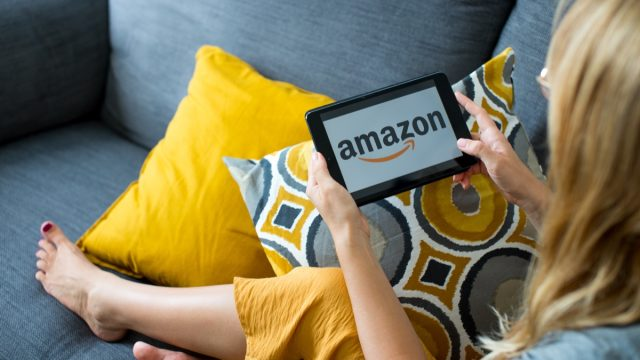 Poznan, Poland, 3.09.2019. Close up on woman's hands holding tablet with Amazon logo. Young woman using tablet with Amazon logo on the screen at cozy home on sofa in living room.