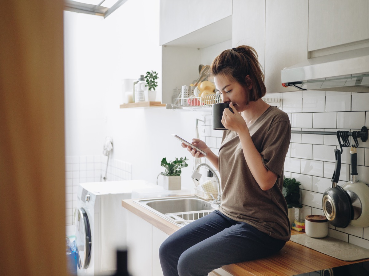 woman drinking coffee while sitting on kitchen counter and working on smart phone in morning at home.