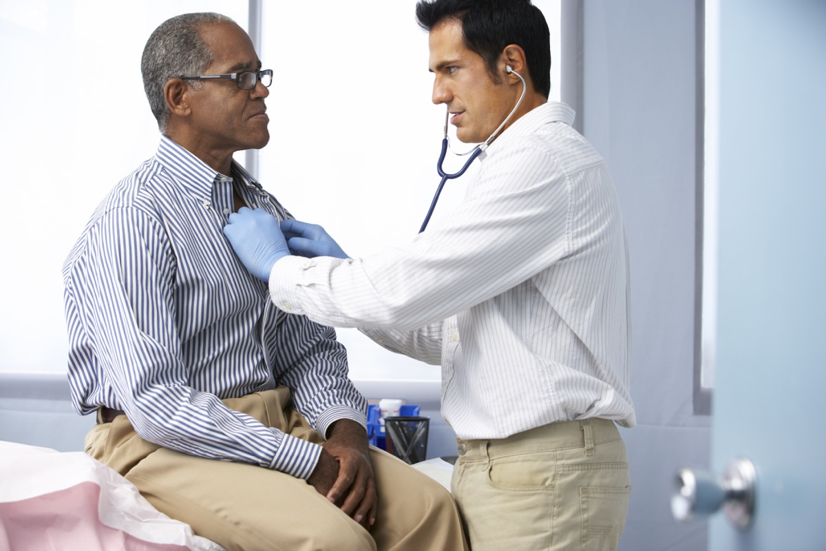 Doctor In Surgery Listening To Male Patient's Chest Using A Stethoscope