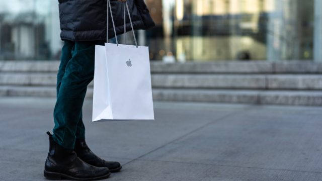 NEW YORK - FEBRUARY, 2020: Woman holding Apple shopper in the street. Apple Inc. is an American multinational technology company headquartered in Cupertino, California.