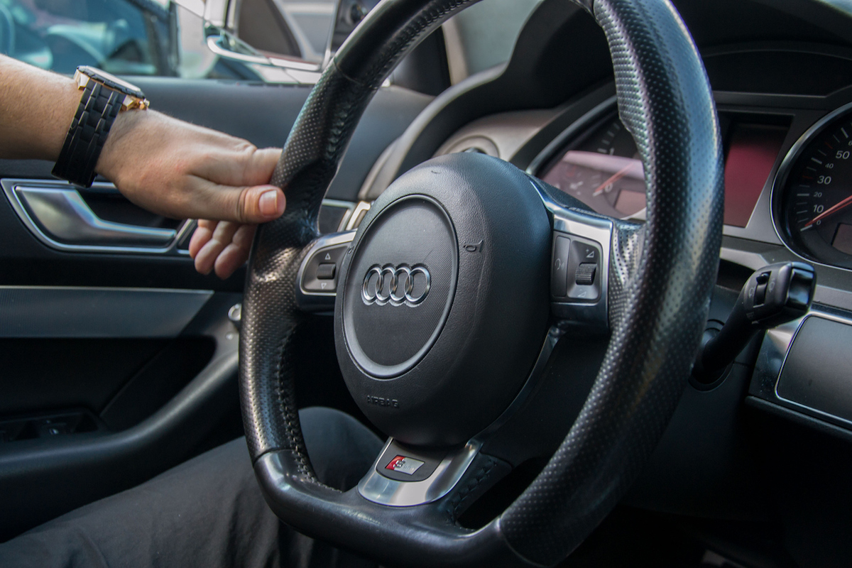 Man hands holds steering wheel of Audi