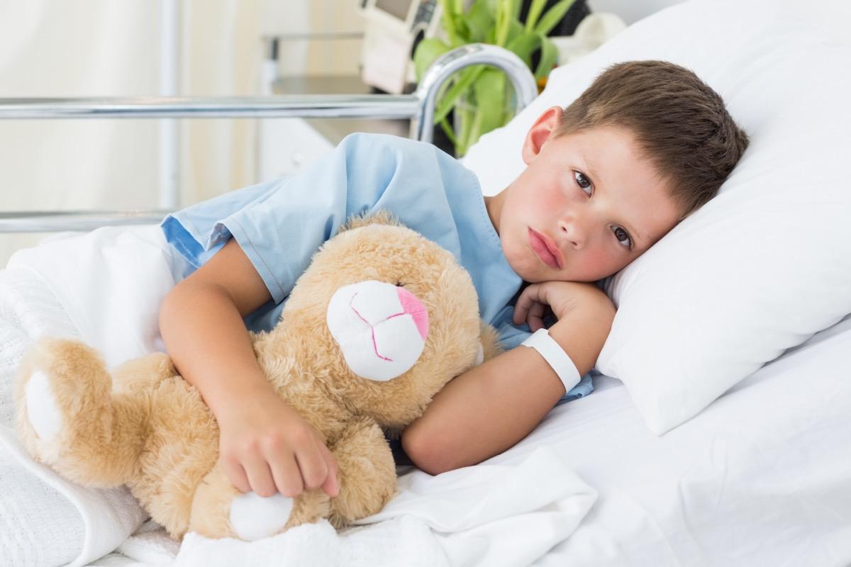 boy sick in hospital bed holding teddy bear