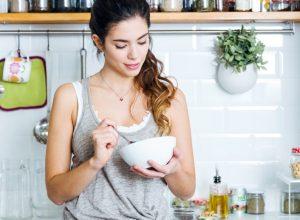 Woman eating breakfast in kitchen