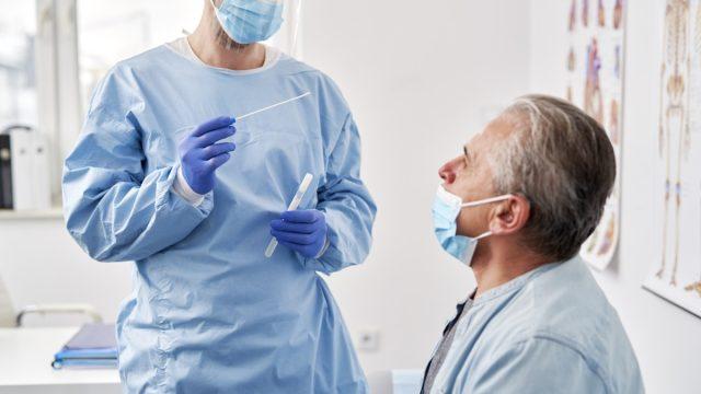 Senior before medic taking sample for coronavirus testing