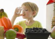 Thirsty child drinking orange juice from the refrigerator.
