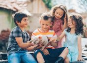 Four children sitting and holding a piglet on a farm