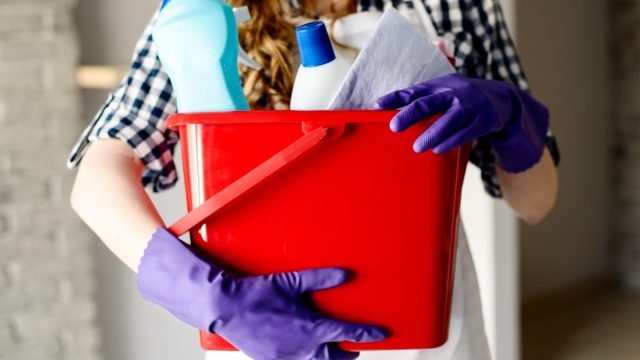 Close up of woman's hands holding bucket full of cleaners