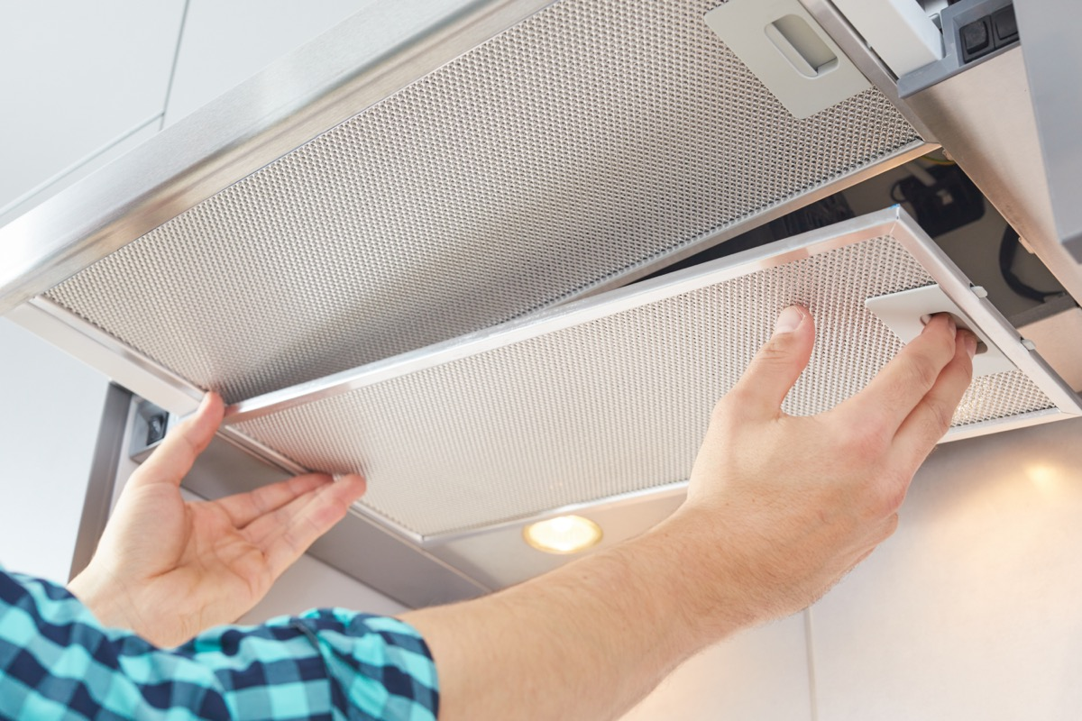 two hands cleaning range hood over stove
