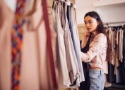 woman browsing and looking to buy summer clothes in a women's boutique