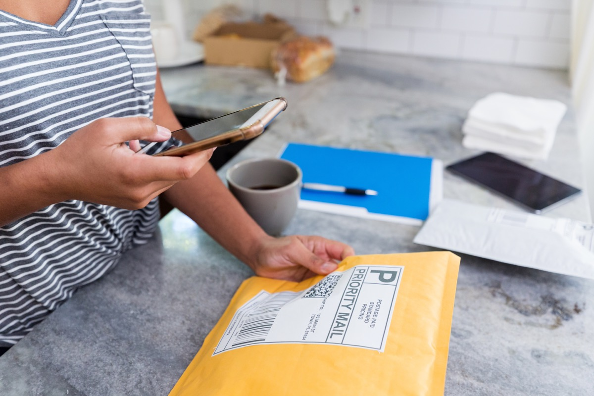 An unrecognizable woman uses a mobile app on her smart phone to prepare a package for mailing.